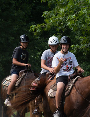 Three boys on horseback.